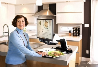 Frau in Küche liest mit Kameralesegerät ein Kochbuch